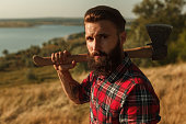 Handsome bearded lumberjack in checkered shirt holding axe on shoulder and looking at camera while standing in amazing countryside
