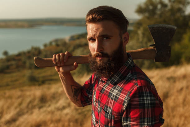 Bearded male with axe in countryside Handsome bearded lumberjack in checkered shirt holding axe on shoulder and looking at camera while standing in amazing countryside forester stock pictures, royalty-free photos & images