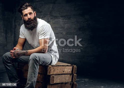istock Bearded male with tattoo on arm dressed in a white t shirt sits 987595136