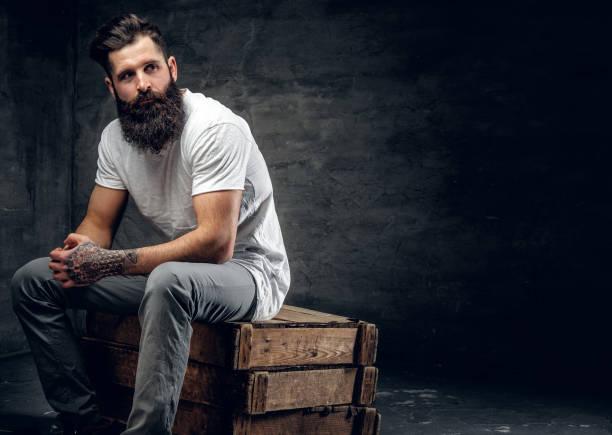 bärtiger mann mit tattoo auf arm, bekleidet mit einem weißen t-shirt sitzt - modedetails stock-fotos und bilder
