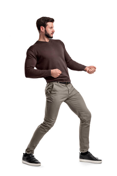 A bearded man a jumper and pants tries to pull a strong invisible rope on a white background. A bearded man a jumper and pants tries to pull a strong invisible rope on a white background. Test of strength. Heavy catch. Pull rope. pulling stock pictures, royalty-free photos & images