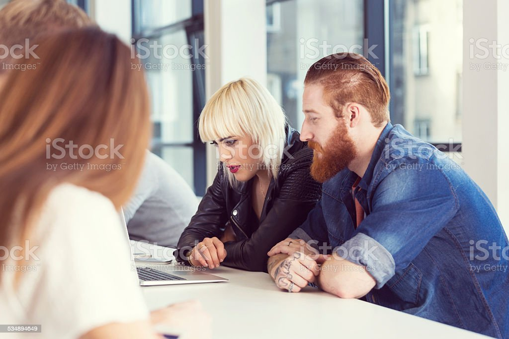 Bearded man and blonde woman working on laptop Start-up business team. Focus on bearded man sitting at the table in an office with his blonde friend and working on laptop.  2015 Stock Photo