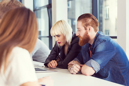 Bearded Man And Blonde Woman Working On Laptop Stock Photo - Download Image Now