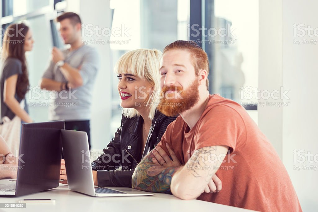 Bearded man and blonde woman working on laptop Bearded man sitting at the table in an office with his blonde friend and working on laptop. Two young people talking in the background. 2015 Stock Photo