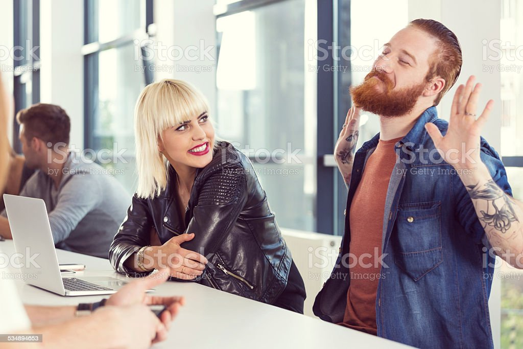 Bearded man and blonde young woman working on laptop Start-up business team. Focus on bearded man talking with his blonde friend. 2015 Stock Photo
