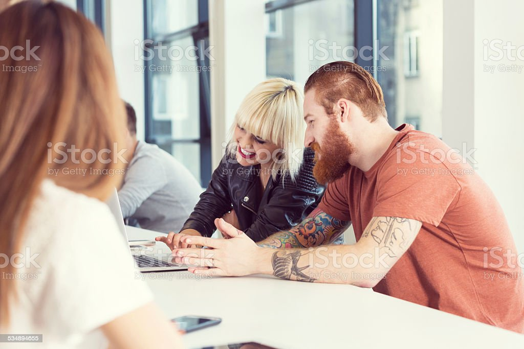 Bearded man and blonde young woman working on laptop Start-up business team. Focus on bearded man sitting at the table in an office with his blonde friend and working on laptop.  2015 Stock Photo