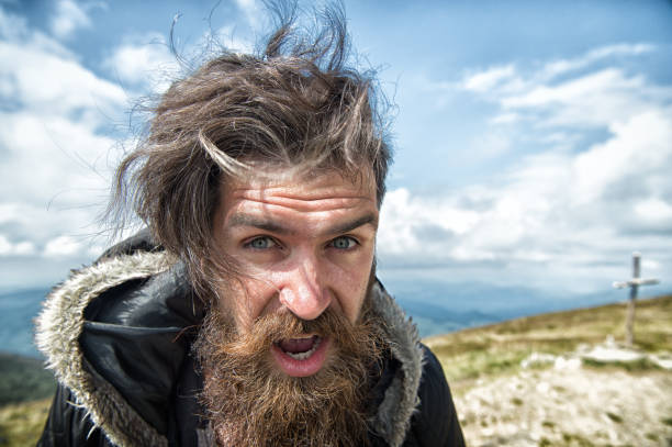 bearded man, brutal caucasian hipster with moustache on windy mountain stock photo