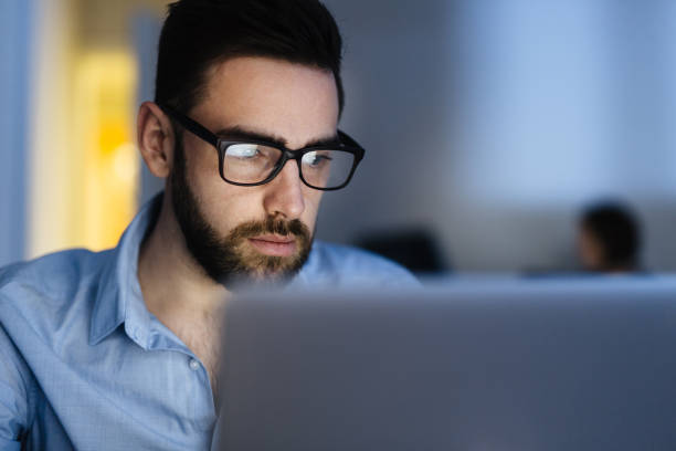 bearded man busy working late - concentration stock photos and pictures