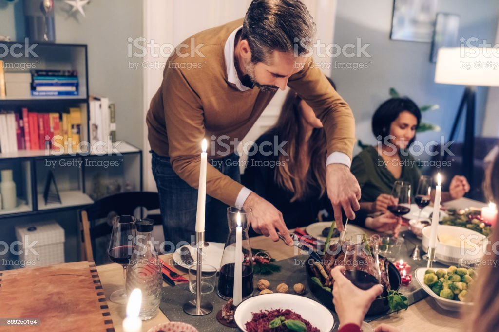 bearded man carving celebrity roast at christmas table stock photo