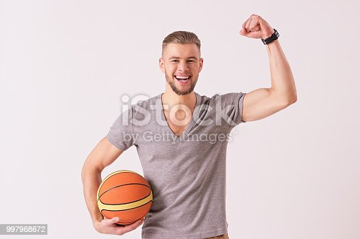 Attractive bearded man keeping arm raised and smiling while isolated on white background. Young hipster celebrating victory and holding basketball ball in hand. Successful sportsman. Healthy lifestyle