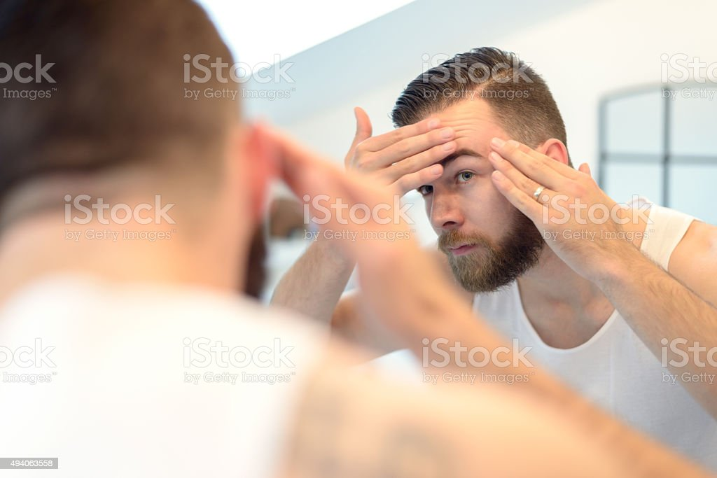 Bearded man checking his complexion stock photo