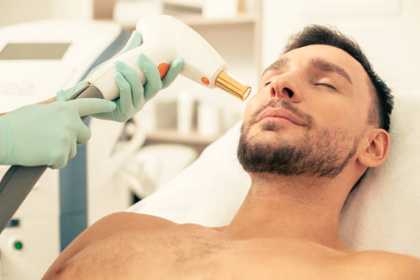 Bearded man closing his eyes at the laser treatment in clinic stock photo