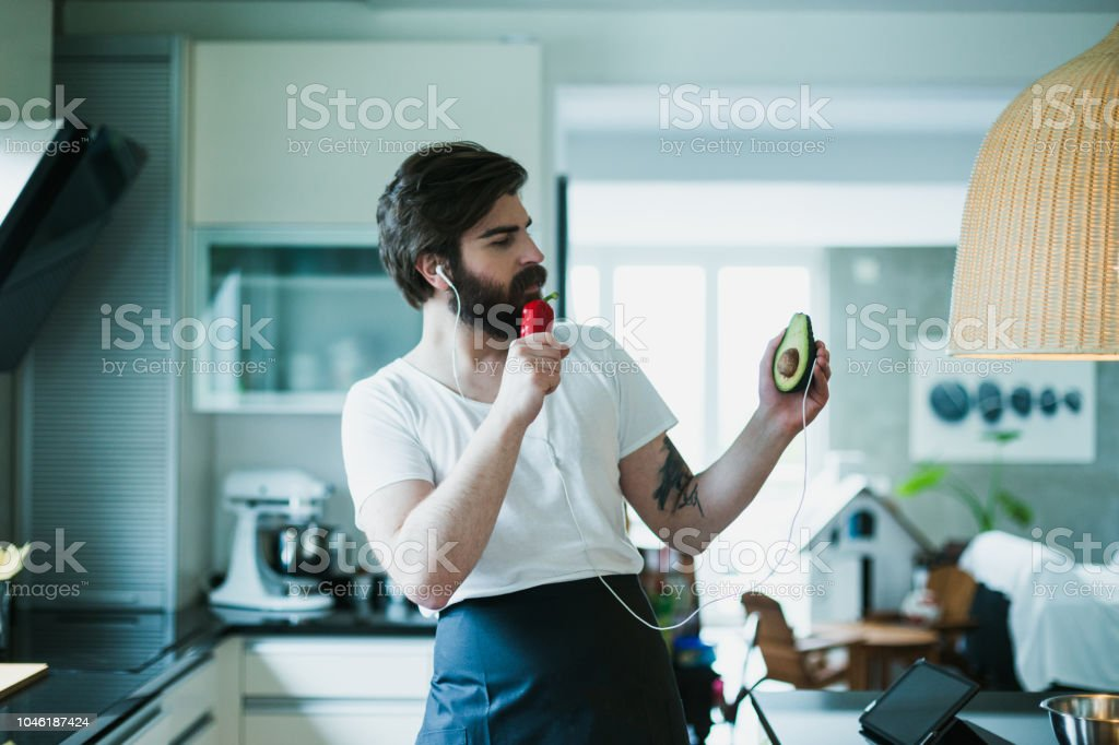 Bearded man cooking and having fun in the kitchen stock photo