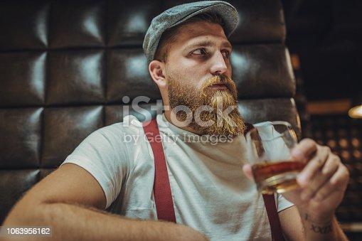 One man, modern bearded man sitting in bar alone, drinking whiskey.