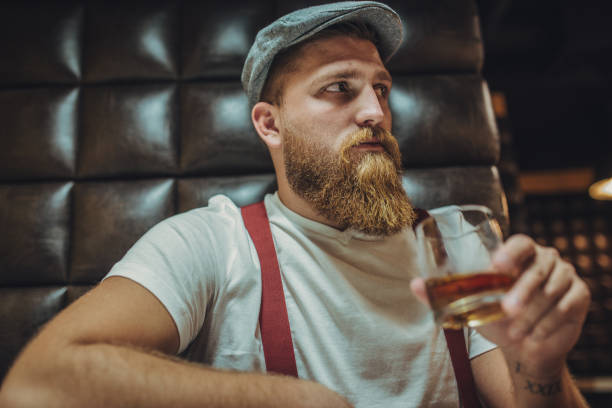 bearded man drinking whiskey - mascolinità foto e immagini stock