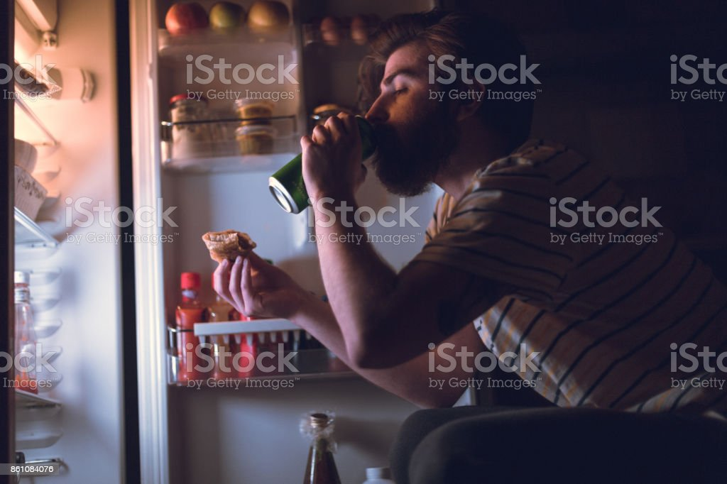 Bearded man eating and drinking beer during the night stock photo