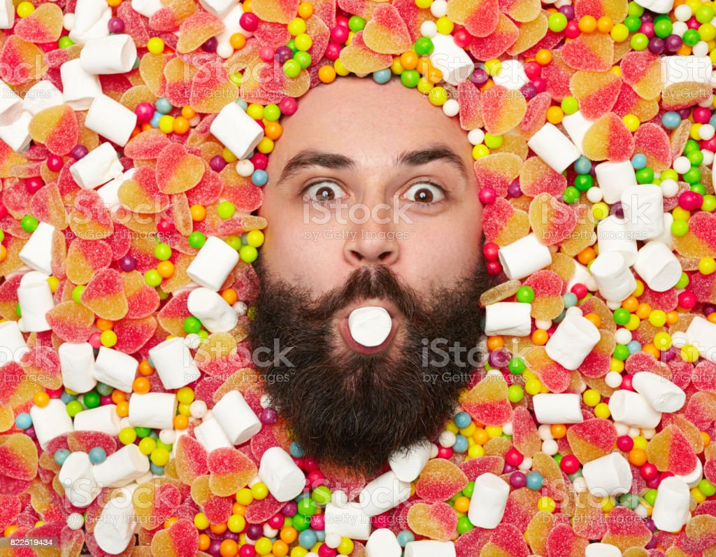 Bearded man holding marshmallow in mouth stock photo
