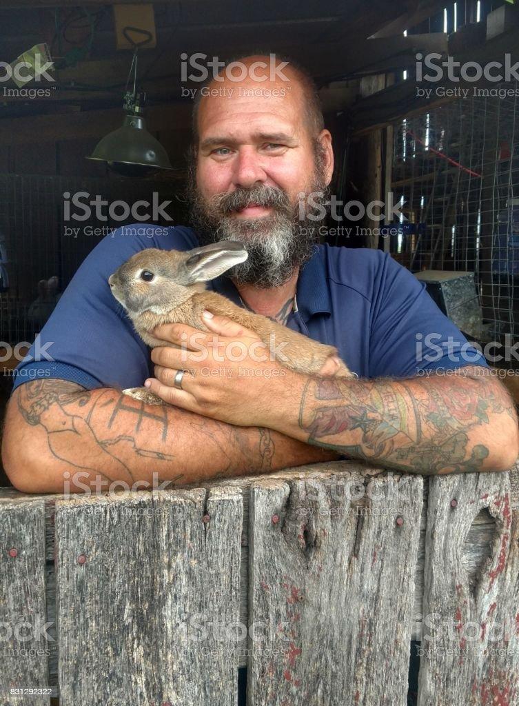 Homem barbudo segurando coelho - foto de acervo
