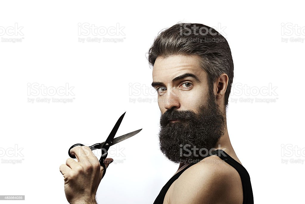 Bearded man holding scissors and wearing undershirt on white background stock photo