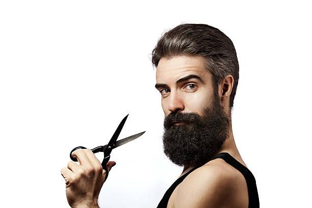 bearded man holding scissors and wearing undershirt on white background - 膝蓋以上 個照片及圖片檔