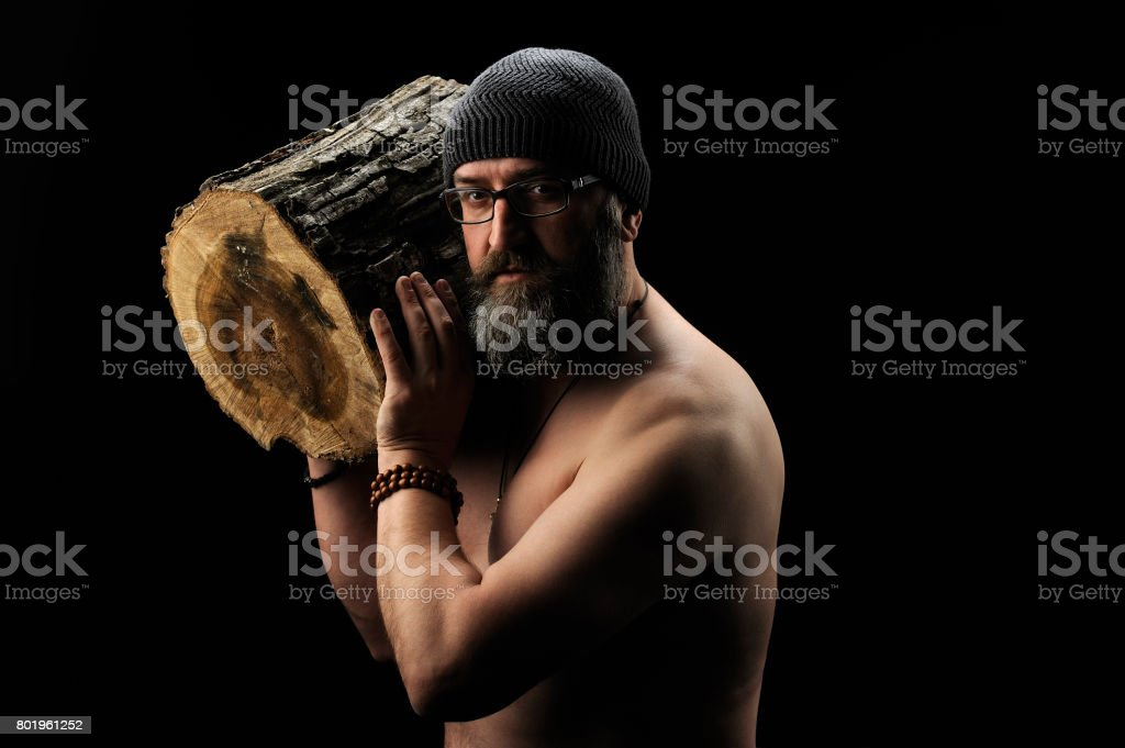 Bearded man holds a log in his hand, black background 2 stock photo