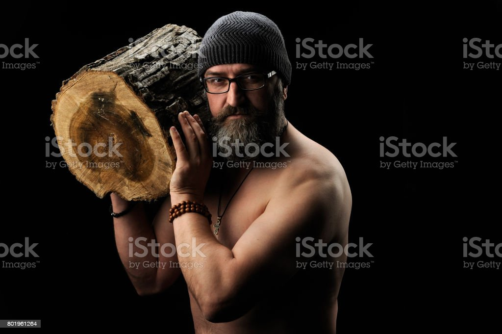 Bearded man holds a log in his hand, black background 3 stock photo