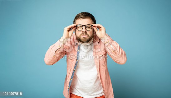 Young bearded man holds glasses on his face with his hands and peers into the distance trying to see something. Isolated on a blue background.
