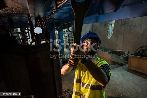 Bearded man in a factory basement repairs a giant dark concrete mixer engine with a large wrench