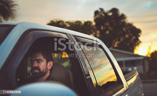 Handsome man in his 30's with a rugged looking beard in a truck with the evening sunset reflected in the window. Cheerful candid and beautiful nature