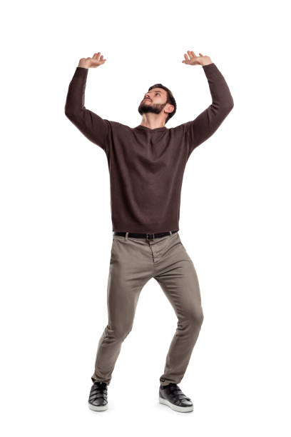a bearded man in casual clothes attempts to hold something heavy from above on a white background. - carrying stock pictures, royalty-free photos & images