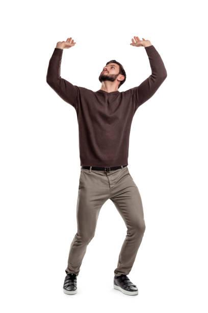 ein bärtiger mann in freizeitkleidung versucht, etwas schwer von oben auf einem weißen hintergrund zu halten. - arme hoch stock-fotos und bilder