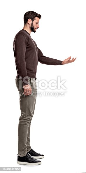 A bearded man in casual clothes stands still in a side view and looks down to his empty outstretched hand. Invisible object. New invention. Showing new goods.
