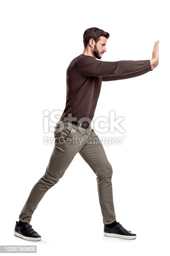 A bearded man in casual clothes tries to push a heavy object with both arms with one leg put in front for balance. Physical force. Test of strength. Man at work.