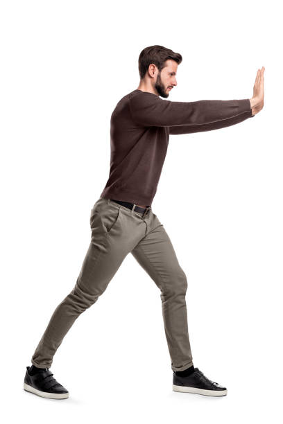 a bearded man in casual clothes tries to push a heavy object with both arms with one leg put in front for balance. - spingere foto e immagini stock