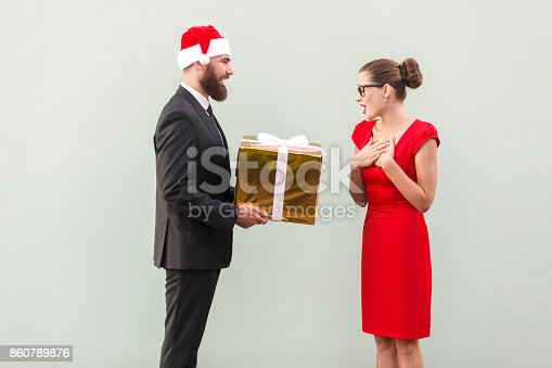 istock Bearded man in red cup give a present beautiful woman 860789876