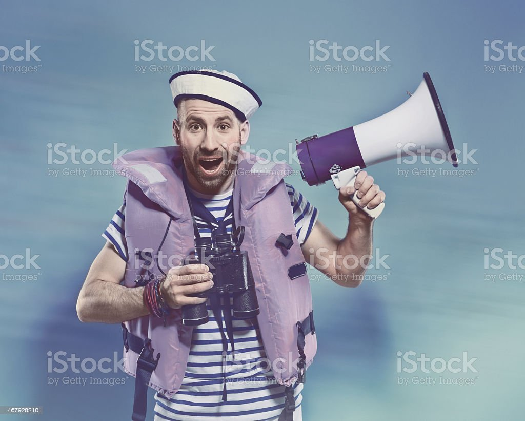 Bearded man in sailor style outfit holding binoculars and megaphone Portrait of surprised bearded sailor man wearing white and blue striped clothing, sailor hat and life vest, holding binoculars and megaphone in hands. Standing against blue background and shouting at camera. Studio shot, one person. 2015 Stock Photo