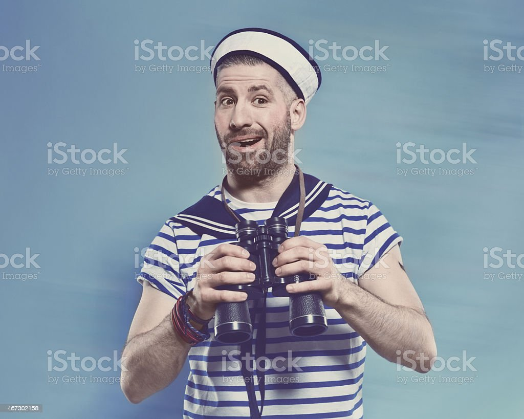 Bearded man in sailor style outfit holding binoculars Portrait of surprised bearded sailor man wearing white and blue striped clothing and sailor hat, holding binoculars in hands. Standing against blue background. Studio shot, one person. 2015 Stock Photo
