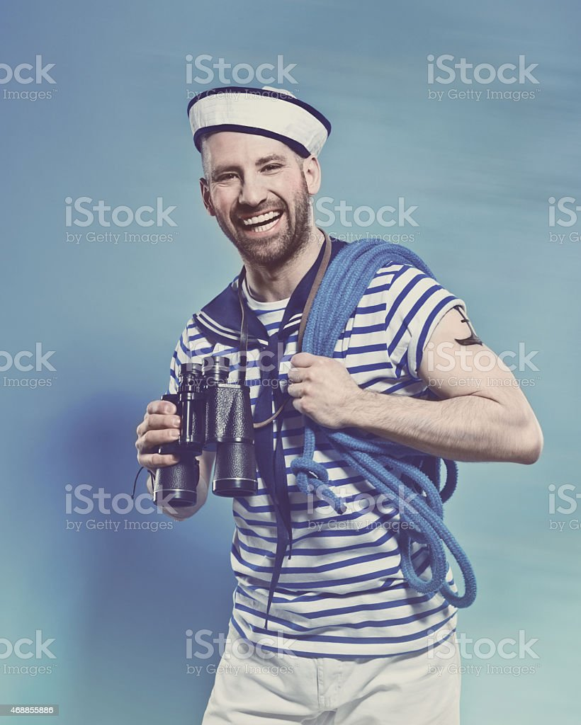Bearded man in sailor style outfit holding binoculars Portrait of happy bearded sailor man wearing white and blue striped clothing and sailor hat, holding rope on shoulder and binoculars in hand. Standing against blue background, laughing at camera. Studio shot, one person. 2015 Stock Photo