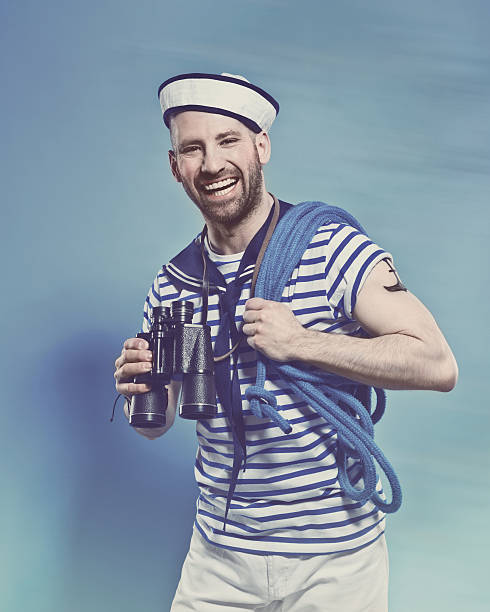 Bearded man in sailor style outfit holding binoculars Portrait of happy bearded sailor man wearing white and blue striped clothing and sailor hat, holding rope on shoulder and binoculars in hand. Standing against blue background, laughing at camera. Studio shot, one person. sailor suit stock pictures, royalty-free photos & images