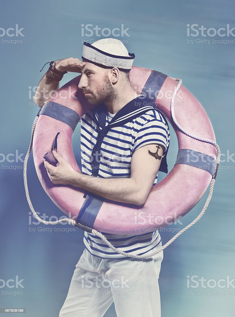 Bearded man in sailor style outfit holding lifebuoy Portrait of bearded sailor man wearing white and blue striped clothing and sailor hat, holding lifebuoy on shoulder and looking away. Standing against blue background. Studio shot, one person, side view. 2015 Stock Photo