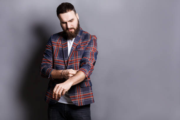 Bearded man in shirt adjusting sleeves copy space stock photo
