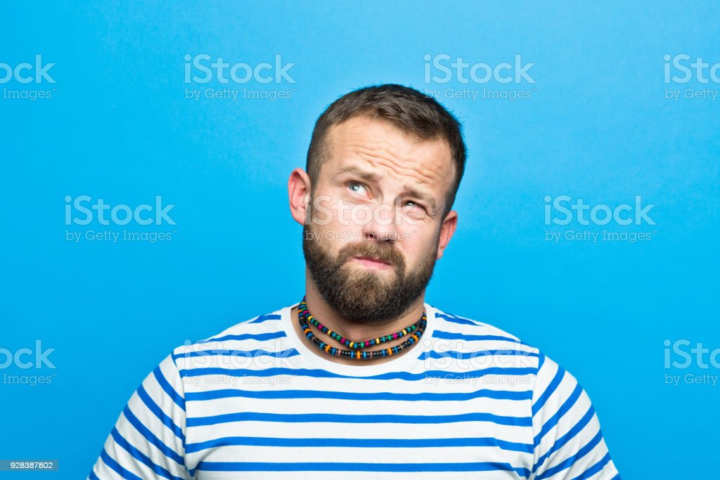 Bearded man in striped t-shirt making up his mind, sailor style Portrait of happy bearded man wearing striped t-shirt looking up. Studio shot, blue background. 30-34 Years Stock Photo