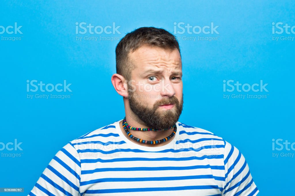 Bearded man in striped t-shirt making up his mind, sailor style Portrait of happy bearded man wearing striped t-shirt looking at camera. Studio shot, blue background. 30-34 Years Stock Photo