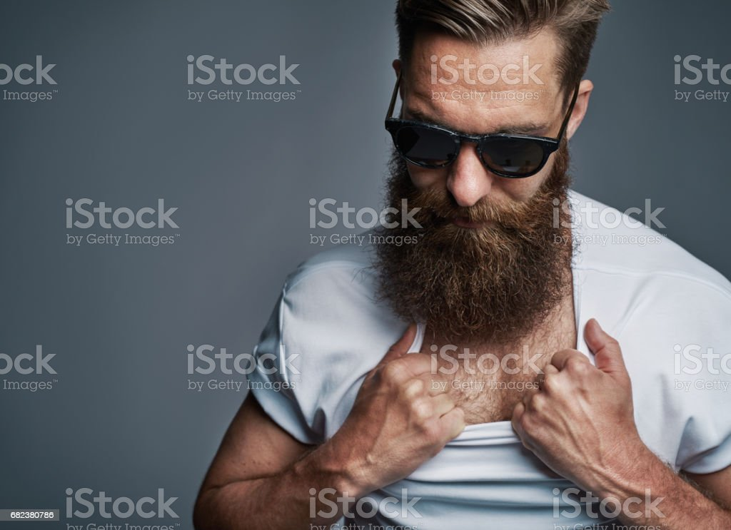 Bearded man in sunglasses showing chest hair royalty-free stock photo