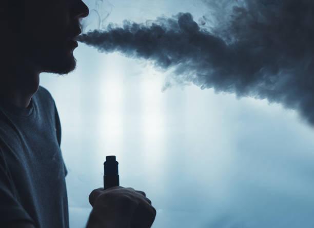 전자 담배 근접 촬영에서 증기의 구름에서 수염된 남자. vaping 남자 - 전자담배 뉴스 사진 이미지