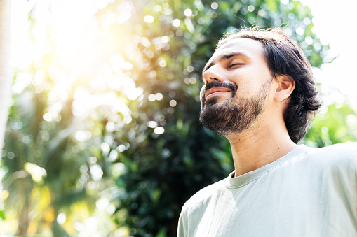 A bearded man is meditating outdoor in the park with face raised up to sky and eyes closed on sunny summer day. Concept of meditation, dreaming, wellbeing and healthy lifestyle