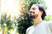 istock A bearded man is meditating outdoor in the park with face raised up to sky and eyes closed on sunny summer day. Concept of meditation, dreaming, wellbeing healthy lifestyle 1202966610