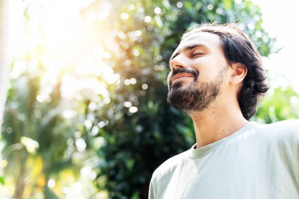 ein bärtiger mann meditiert im freien im park mit erhobenem gesicht und geschlossenen augen am sonnigen sommertag. konzept der meditation, träumen, wohlbefinden gesunder lebensstil - gelassene person stock-fotos und bilder