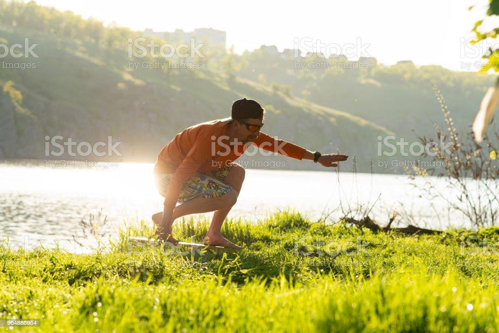 Bearded man is training on the balance board and having fun royalty-free stock photo