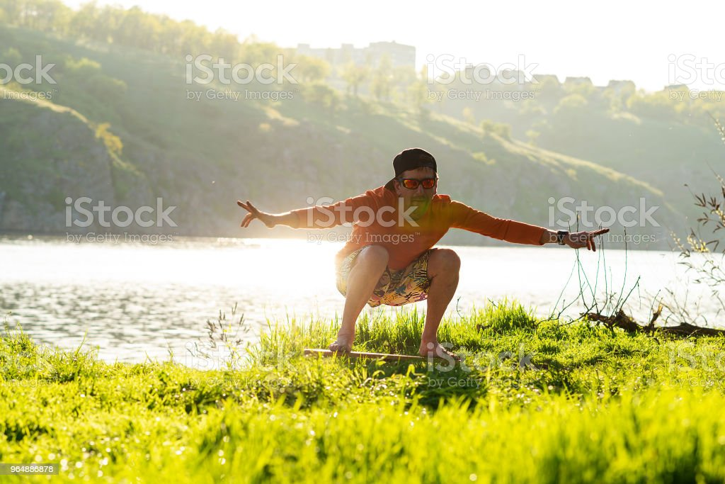 Bearded man is training on the balance board royalty-free stock photo